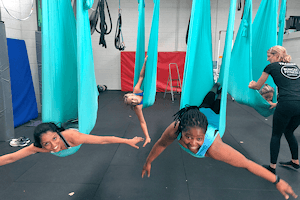Corporate groups enjoy the Dragonfly pose at aerial yoga